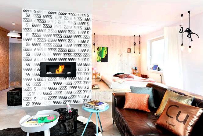 Обустройство гостиной с кухней черной osb плитой и перфорированным кирпичом на заднем плане